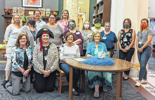 After years of serving the community through the Carnegie Public Library, staff members Jeanne Miller (second from right seated, 35 years) and Kay Oughterson (pictured at the far right seated, 20 years) will be retiring. On Friday, their fellow staff members held a celebration in their honor with a tropical theme.