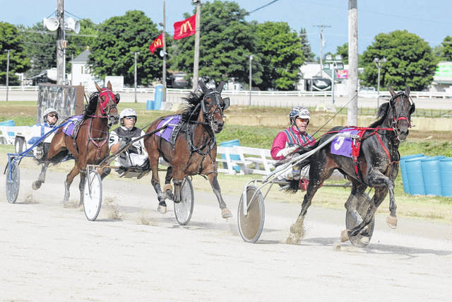 Horses pass the grandstand in the sixth race Wednesday, July 22, 2020 at the Fayette County Fair. (l-r); Hillz, driven by Thomas Litt; Hometown Honey, driven by Jeff Smith and Full Of Truth, driven by Kevin Beckstedt. There will be 14 races at the fair Saturday, beginning at noon. Racing will conclude with the D.E. Mossbarger Fayette County Classic.