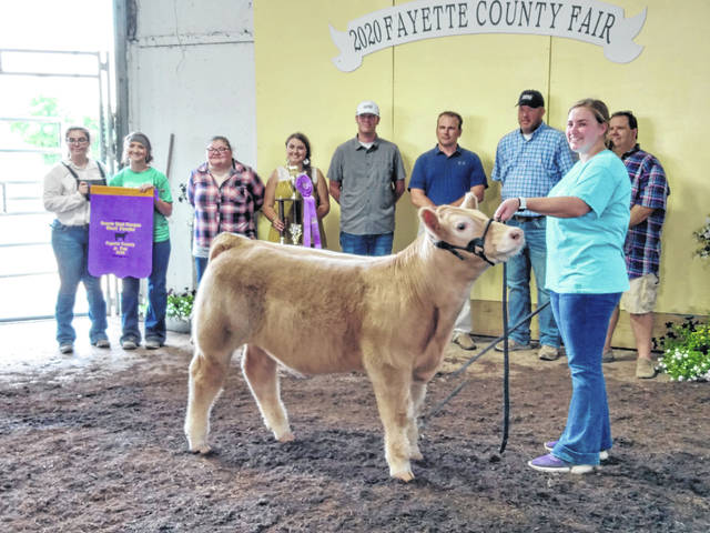 Madison Riley's project was named the Reserve Grand Champion Beef Feeder Tuesday afternoon. Pictured (L to R): Cassie Baird, Macie Riley, Madison Riley, McKenzie Riley, seller Bricen Hess, judge Joe Beckett, seller Brad Hess, Meri Grace Carson (holding animal) and Shane Riley.