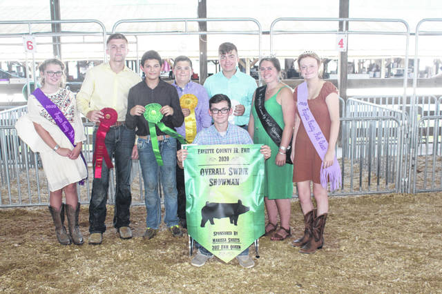 Zander Ivey (seated) won the overall swine showman for the third straight year. From left to right behind Ivey are: Pork Princess Emma Bower, second place showman Kylan Knapp, fifth place showman Konner May, fourth place showman Dane Wilt, third place showman Drake Sharp, and Fayette County Fair Queen Aubrey Schwartz and Fayette County Pork Queen Laikyn Hughes.