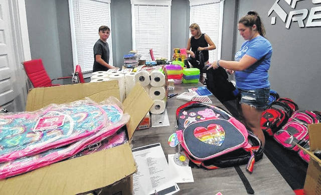 "Audra Everhart (back, right), Justin Everhart (left) and Aubrey Schwartz (front) assisted with this year's ""Fill The Backpacks"" by filling several backpacks with donated school supplies."