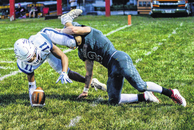 Washington's Traeton Johnson (11) gets tangled up with a Minford player as the two go out of bounds battling for the ball during the season-opening game at Minford Friday, Aug. 28, 2020 in Scioto County.