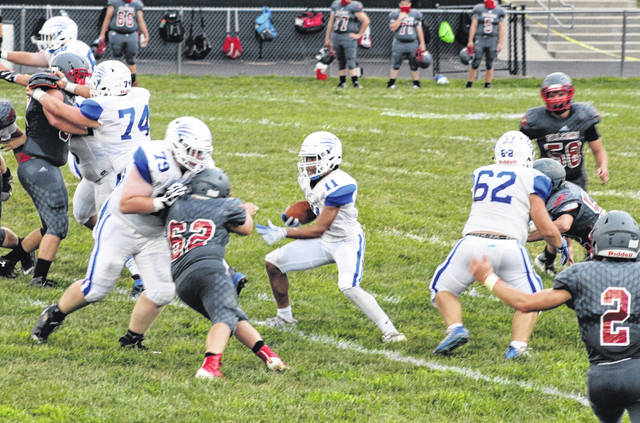 Washington's Traeton Johnson (11) carries the ball during the game at Minford Friday, Aug. 28, 2020. Also pictured for the Blue Lions are (l-r); Sterling Smith (74), Cal Wightman (79) and Chris Wilson (62).