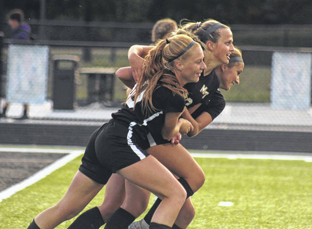 Magarah Bloom (front) and Jana Griffith (back) celebrate with Kaylie Lott after Lott scored during the first half of a Frontier Athletic Conference match against McClain Tuesday, Sept. 15, 2020 at Miami Trace High School.