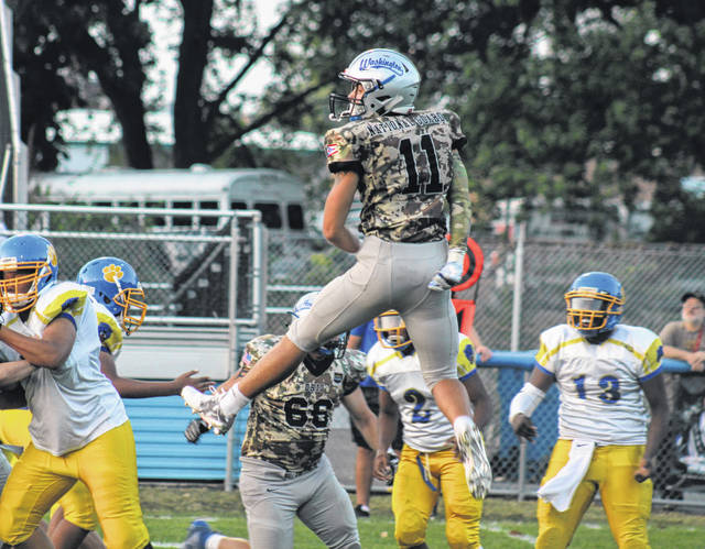 Washington Blue Lion senior Garitt Leisure (11) leaps high into the air in an attempt to block a pass during the game against Ponitz Tech Friday, Sept. 20, 2019.