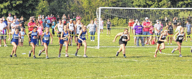 Washington High School (at left) and Miami Trace High School girls runners are pictured at the start of the high school race at Mitchell Park in Greenfield Wednesday, Aug. 26, 2020. (l-r); Washington's Mia Moats, Diya Patel, Kayli Merritt, Maggie Copas and Cloe Copas and Miami Trace's Lorelei King, Kaelin Pfeifer and Mallory Conklin.