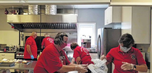 Jeffersonville Lions Club members held a fish fry prior to a firework celebration over the weekend after postponing its usual July 4th celebration. Pictured are the members working to get meals out to the public.
