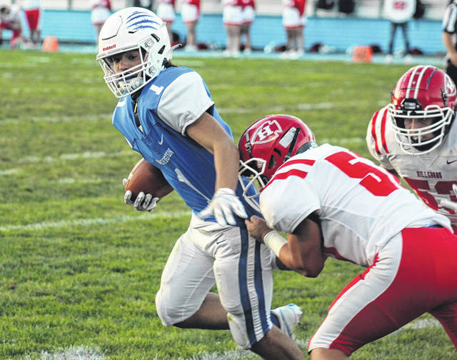 Washington senior Trevin Downing tries to pull away from a Hillsboro defender during the first home game of the season for the Blue Lions Friday, Sept. 18, 2020.
