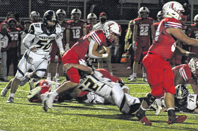 Miami Trace senior Luke Henry (52) makes the tackle during a Division III playoff game at London High School against the Red Raiders Friday, Oct. 16, 2020. At left is senior Ashton Curtis (50).