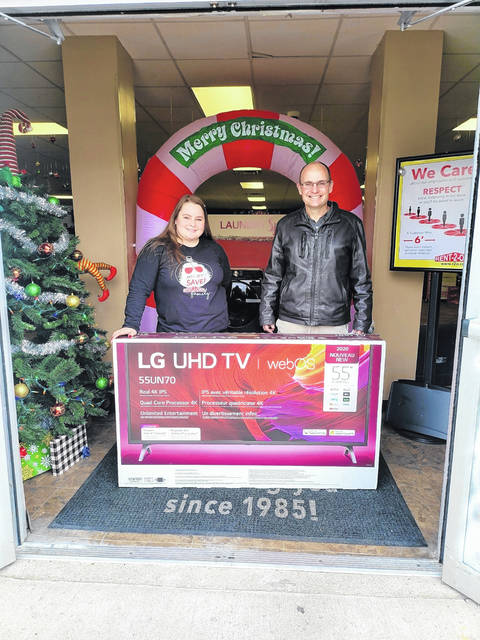 "The Fayette County Family YMCA is offering a variety of opportunities for the community this holiday season to further youth development, healthy living and continue social responsibility. Pictured are Rent2Own Store manager, Lonette Manley, and Fayette County Family YMCA CEO Doug Saunders with the television being donated for a ""Freeze The Gain"" prize."
