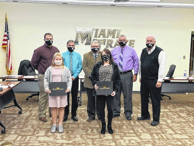 "Savannah Rose (left), seventh grade student at the middle school, and Cheyenne Carpenter (right), nine grade student at the high school, were honored at the Miami Trace Board of Education meeting Monday for winning the ""Write in Red' contest. Pictured behind the two girls are (left to right): MT board members Rob Dawson, David Miller, Bruce Kirkpatrick, Charlie Andrews, and Mike Henry."