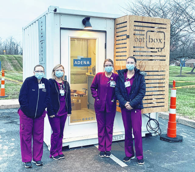 """Adena staff with one of the pod structures, known as """"ootBoxes,"""" that allow for curbside testing even during the winter months."""