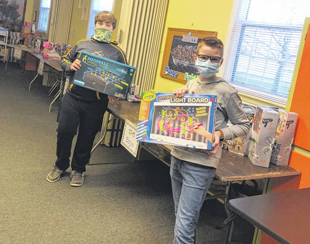 Miami Trace Middle School student council members sorted toys at All Saints Church on Wednesday in preparation for their SOCKS (Spirit of Christmas for Kids) present giveaway this weekend. Pictured are Luke Bennett (left) and Eyan Taulbee (right).