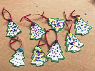 Students from Mrs. Homola's fifth grade Miami Trace Elementary School Homeroom recently decorated a number of tree ornaments. Pictured are various students with their completed project.