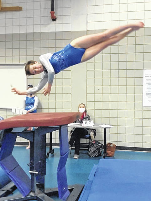 Abby Rose, Washington High School sophomore, 1/2 on 1/2 off twisting over vault table.