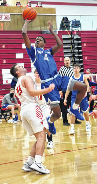Washington Blue Lion senior Micai Claggett (4) puts up a shot over Jackson junior Evan Spires during a Frontier Athletic Conference game at Jackson High School Saturday, Jan. 9, 2021.