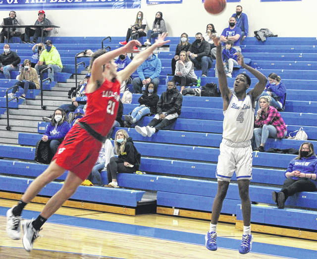 Washington senior Micai Claggett launches a three-point shot during a Frontier Athletic Conference game against Jackson Friday, Jan. 29, 2021 at Washington High School. Defending for Jackson is senior Braxton Hammond.