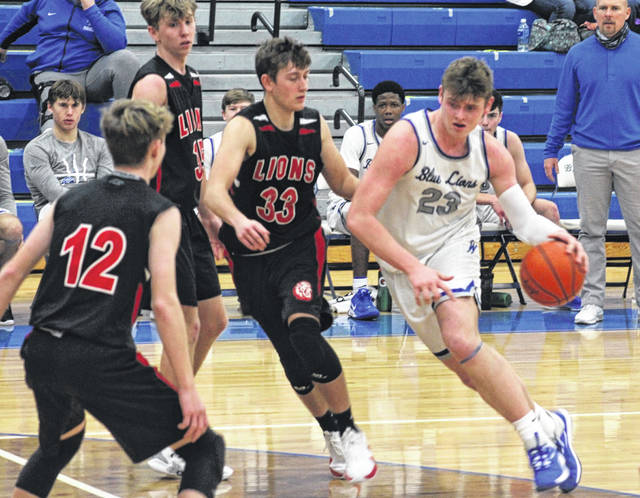 Washington Blue Lion sophomore Tanner Lemaster (23) drives into the lane during a non-conference game against Fairfield Tuesday, Jan. 5, 2021 at Washington High School. Pictured for Fairfield are senior Tucker Watson (33) and junior Koben Zink (12).