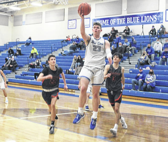 Washington sophomore Tanner Lemaster (23) takes the ball to the basket for two of his game-high 29 points against the Wilmington Hurricane Monday, Jan. 18, 2021 at Washington High School. Pictured for Wilmington are junior Cole Bernhardt (left) and senior Matthew Butcher (right).