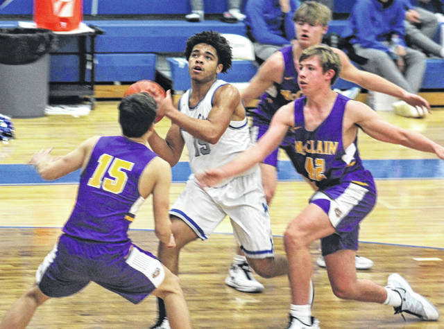 Washington Blue Lion sophomore Traeton Johnson (15) takes the ball to the basket surrounded by a trio of McClain Tigers, including senior Camden Closson (15) and junior Wesley Potts 42.