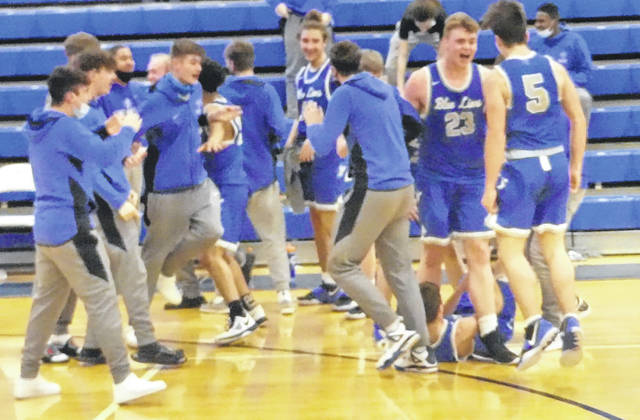 Members of the Washington Blue Lion basketball team celebrate after a 67-62 win at Chillicothe on Friday, Jan. 22, 2021 that snapped a 32-game losing streak for the team.
