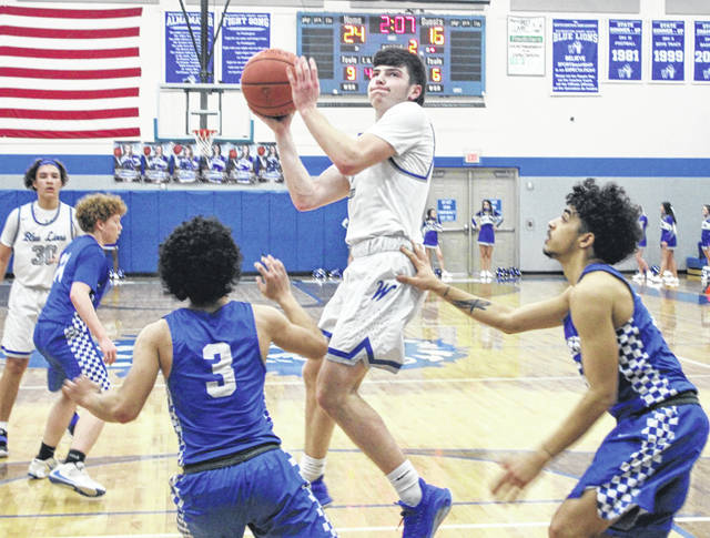 Washington senior Brice Cartwright puts up a shot in the lane during a Frontier Athletic Conference game against Chillicothe Thursday, Feb. 4, 2021 at Washington High School. Also pictured for the Blue Lions is freshman Isaiah Haithcock.