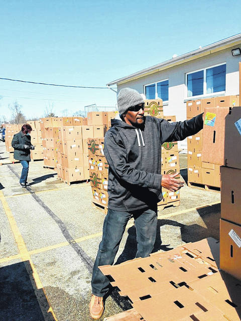 """Two truckloads and over 3,600 boxes of food have been given away this week as part of the """"Feed Fayette"""" program with the help of many area churches. It is held at South Side Church of Christ at 921 S. Fayette St. in Washington Court House. Thanks to the program """"Farmers to Families"""" — where the food comes from — and a plethora of local churches, many residents will continue to eat. The program is currently expected to continue through the month of April and is held every week at noon. Pictured is Sam Eddings, one of the many volunteers who takes time each week to ensure the food makes it to the people."""