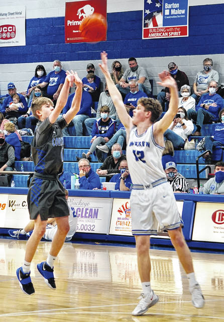 Washington High School freshman John Wall (left) launches a shot while guarded by Warren junior Hunter Haines during a Division II Sectional semifinal game Thursday, Feb. 25, 2021 at Warren High School. The Warriors won the game, 67-19.