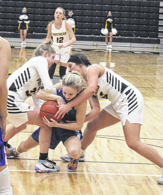 Miami Trace juniors Emma Pitstick (left) and Libby Aleshire battle Washington sophomore Allie Mongold for possession during a Frontier Athletic Conference game at Miami Trace High School Saturday, Feb. 6. 2021.