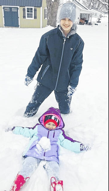 Elijah Kerwood (13) and Sadie Dunn (4) playing in the snow on Tuesday.