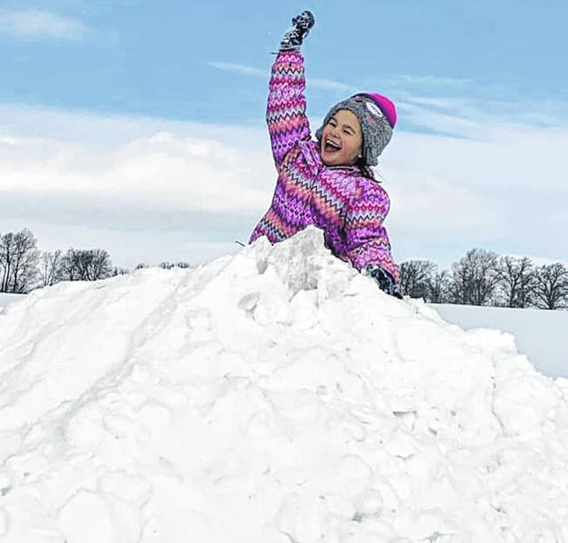 Paislee conquering a snow pile.