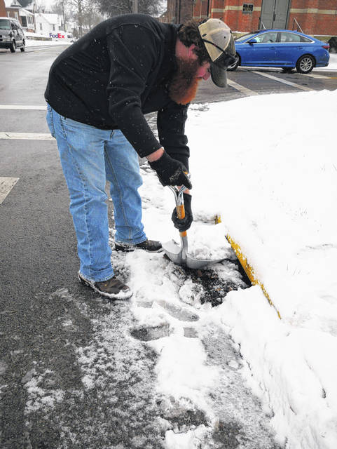 Malcolm Miller with Fayette Soil & Water Conservation District clears away snow from a drain near the Carnegie Public Library.