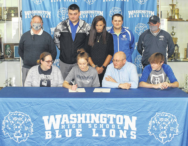 Washington High School senior Brooklyn Foose, seated, second from left, on Monday, March 8, 2021, signs a letter of intent to attend Shawnee State University, where she will continue her academic and athletic careers. She was joined for the occassion by her parents, Tessa Distel, left and Rick Foose and her brother, R.J. Foose and (standing, l-r); Shawnee State tennis coach Steve Boone, Washington High School assistant tennis coach Seth Leach, Washington High School head tennis coach Samantha Bihl, Washington High School girls bowling coach Anthony Amore and Shawnee State bowling coach Bryan Sturgell.