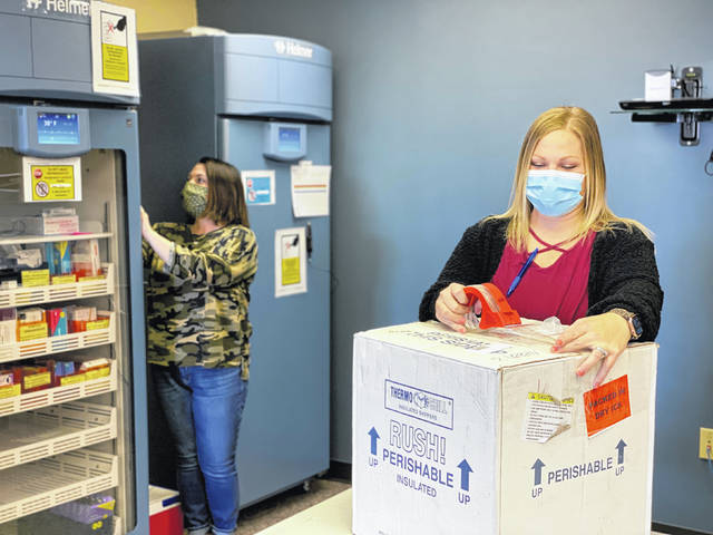 Tracy Dye, RN, BSN, checks, and logs the temperature on a vaccine refrigerator at Fayette County Public Health, and Ashley Roberts, RN, prepares vaccine packaging to be sent back to the shipping company. By the end of this week, Fayette County Public Health will have received their first shipment of the Johnson & Johnson vaccine - the latest vaccine to receive an Emergency Use Authorization (EUA) from the Food and Drug Administration. There are now three vaccines currently approved with an EUA and each has different storage and handling protocols.