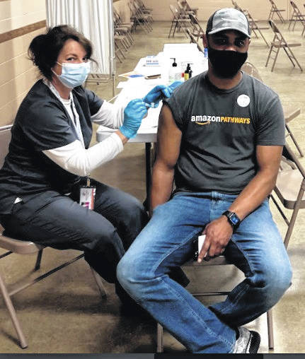 Medical Reserve Corps volunteer Jennifer Wenker vaccinates Corey Brothers at the Fayette County Public Health (FCPH) Moderna clinic. Next week, FCPH will offer both Moderna and Pfizer at its first-dose clinic. Pfizer is currently the only vaccine authorized for 16- and 17-year-olds (parental or legal guardian consent is required).