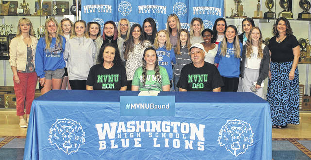 Washington High School senior Lexi Stiffler (seated, middle) is flanked by her parents, Christina and Rob Stiffler and many of her cheerleading teammates and cheer coaches, as well as a couple of her friends from the softball team for which she plays, at her signing ceremony April 8, 2021.