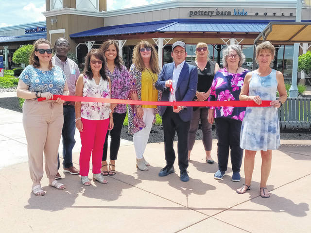 On Thursday, a ribbon cutting was held at Destination Outlets in Jeffersonville with several in attendance including members of the Fayette County Chamber of Commerce. Pictured with the various members of the Chamber of Commerce and representing Destination Outlets were General Manager Jennifer Snyder (at left in blue), Co-managing Partner Alex Hofstedter (center holding scissors) and Administrative Assistant Trish Saunders (at right in navy and pink flower shirt).