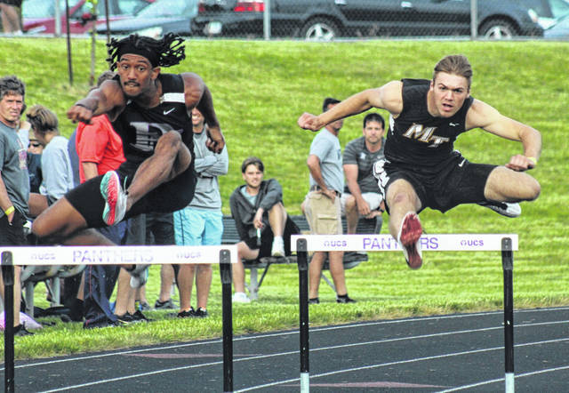Jaden Haldeman, right, of Miami Trace, clears a hurdle in the 300-meter event next to Zemen Siyoum of Pickerington North at the Division I Regional meet at Pickerington North High School Wednesday, May 26, 2021. Haldeman qualified to Friday's finals with the second-fastest prelim time of 38.604.