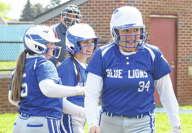 Washington senior Kearria Marcum (34) returns to the dugout after hitting a grand slam home run in the third inning of a Division II Sectional tournament game against Marietta Saturday, May 8, 2021. Also pictured for Washington are senior Emma Funari (5) and freshman Addison Knisley.
