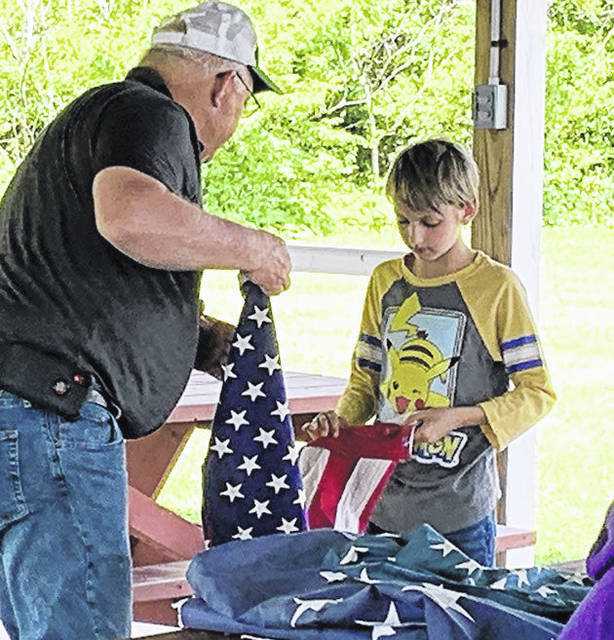 Scout Todd Thornhill works with Fayette County Scout Commissioner Mark Hoppes during preparation for this weekend's flag-retirement ceremony at the Fayette County Museum.