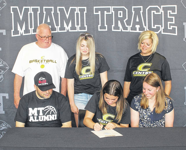 Gracee Stewart, seated, middle, signs a letter of intent to attend Centre College located in Danville, Kentucky, where she will continue her education and her basketball career as a member of the Colonels' women's basketball team. (seated, l-r); Ben Ackley, former head coach of the girls basketball team at Miami Trace; Stewart; Kayla Dettwiller, head girls basketball coach at Miami Trace; (back, l-r); Stewart's family, dad Billy, sister Jessee and mom, Jenny Stewart.