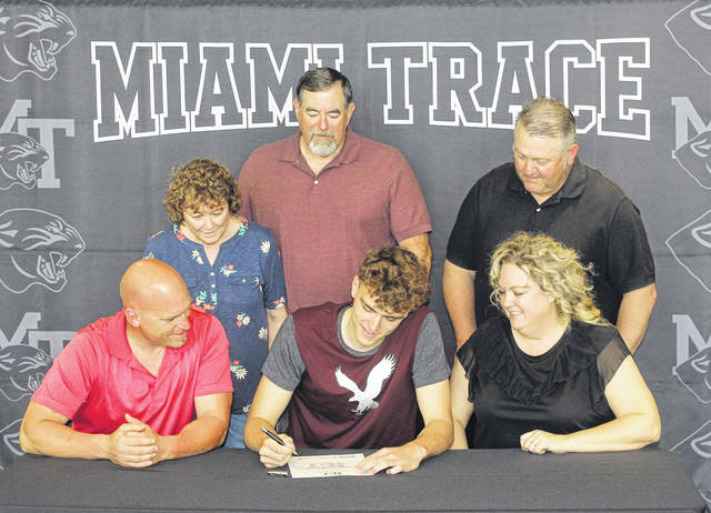 Logan Rodgers, seated, flanked by his parents, Rich Rodgers and Lori Gentry, and signs a letter of intent to attend Evangel University in Springfield, Missouri, where he will continue his education and his basketball career. (standing, l-r); Rodgers' grandparents Trudy Summers and Gary Summers and step-father, Bobby Gentry.