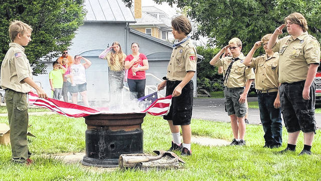 Scouts and brothers, Todd (left) and James Thornhill, lay a flag on the retirement fire during the flag-retirement ceremony held Sunday, June 13 at the county museum.
