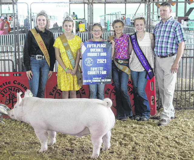 Olivia McLaughlin (holding banner) won fifth place overall market hog at Wednesday's Fayette County Junior Fair Market Hog Show.