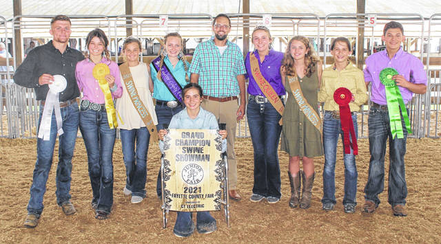Emily Reeves (seated, middle) won the grand champion swine showman prize at Tuesday's Fayette County Junior Fair Swine Showmanship contest. Pictured with Reeves are (left to right): third place winner Kylan Knapp, fourth place winner Lexi Hagler, Swine Princess Emma Hagler, Fair Queen Garren Walker, judge Matthew Nott, Swine Queen Libby Aleshire, Swine Princess Emma Bower, second place winner Alison Reeves, and fifth place winner Konner May.
