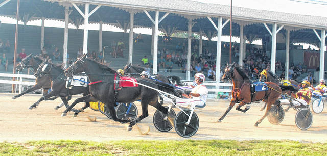 Harness racing returns to the Fayette County Fair Saturday, beginning at noon, with a total of 15 races on the card. The final race of the afternoon will be the annual D.E. Mossbarger Fayette County Classic, with a purse of $9,000. Above, horses pass the grandstand during Wednesday's eighth race.