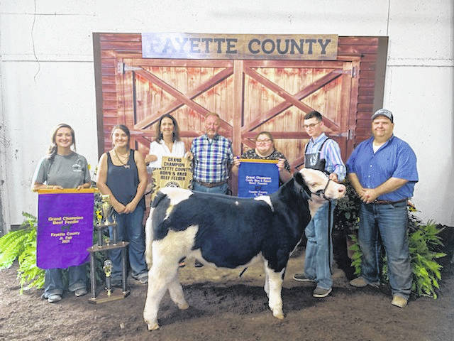 Madison Riley (holding blue banner third from right) claimed the supreme grand champion beef feeder prize on Tuesday afternoon. The beef feeder was shown by Zander Ivey and was bred by Randy and Loretta Miller of Fayette County's Finest Showcattle.