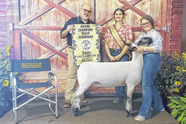 Emily Taylor was named the Reserve Champion of the Market Lamb Show as well as the Overall Sheep Showman on Thursday. Pictured (left-to-right) are: Terry Burks (judge), Abbie Brandt (Fayette County Fair Lamb and Wool Queen), and Emily Taylor.