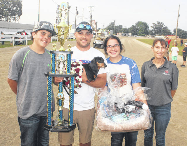 Trevor Justice holds Turbo and a large trophy as Turbo won the inaugural Wiener dog race held at the Fayette County Fair Wednesday, July 21, 2021. (l-r); Kole Justice, Trevor Justice, Kaytlyn Justice and, representing the sponsors of the event, Red Collar Pet Foods of Washington C.H., Brenda Collins.