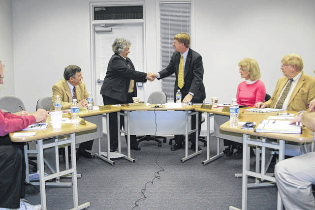 SSCC President Dr. Kevin Boys, standing at right, shakes hands with former Board of Trustees member, the late Kay Ayres, at his first board meeting in 2010.